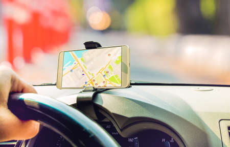 Female driver sitting in the car use mobile smart phone with map gps navigation application