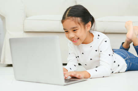 Foto de Happy Asian girl using laptop computer, concept for kid's art and home school. - Imagen libre de derechos