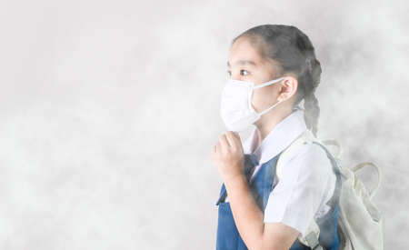Portrait Asian children girl wear  mask to protect PM 2.5 dust and air pollution. Portrait of Thai student wearing protection mask  bad weather, pm2.5 concept backgroundの素材 [FY310140416712]