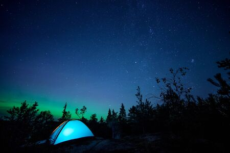 Photo for Night scene with illuminated camping tent, forest, starry sky and northern lights. Long exposure - Royalty Free Image