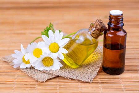 Foto de Essential oil in glass bottle with fresh chamomile flowers, beauty treatment. - Imagen libre de derechos