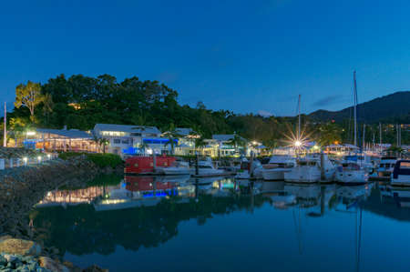 Bay with yachts and restaurants at night. Abell Point Marina, Airlie beach, Australia