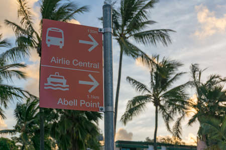 Airlie beach, Australia - February 5, 2017: Street directory to Airlie Central Bus station and Abell Point Marina with palm tree treetops on the background