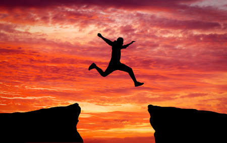 Photo pour Man jumping across the gap from one rock to cling to the other. Man jumping over rocks with gap on sunset fiery background. Element of design. - image libre de droit