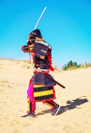 Men in samurai armour with sword running on sand