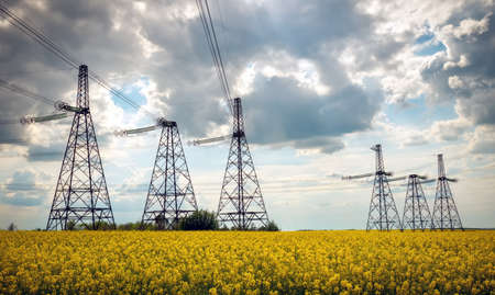 Photo pour Transmission towers in the middle of a yellow canola field in bloom. High voltage power line at Spring - image libre de droit