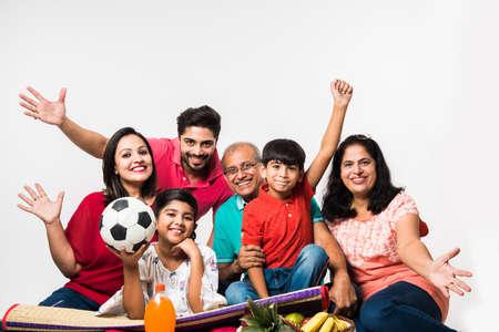 Foto de Indian Kids with parents / grandparents, sitting isolated over white background, studio shot - Imagen libre de derechos
