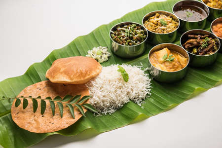 Photo for Traditional South Indian Meal or food served on big banana leaf, Food platter or complete thali.  selective focus - Royalty Free Image
