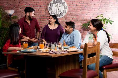 Photo for Indian friends eating or dining in restaurant. Asian people in face for get-together, reunion or celebrating party. Coffee Shop Celebration Friendship Togetherness concept - Royalty Free Image