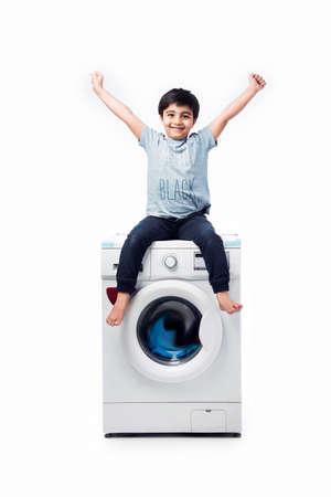 Foto de Indian happy Small boy posing with Washing Machine or Dishwasher against white background - Imagen libre de derechos