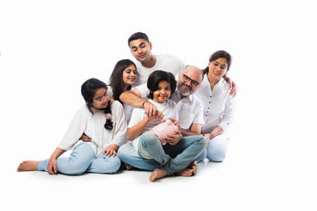 Photo pour Multigenerational Indian family of six holding piggy bank while wearing white cloths and standing against white wall - image libre de droit