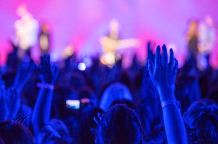 Photo for Open hands raised up in foreground with anonymous guitar player on stage in background - Royalty Free Image
