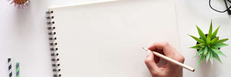 Photo pour A white desk with an open sketchbook and a woman's hand. Drawing. View from above. Creative desk. Mockup. Panorama - image libre de droit