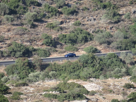 A car drives on an isolated road in the Shomron Mountains
