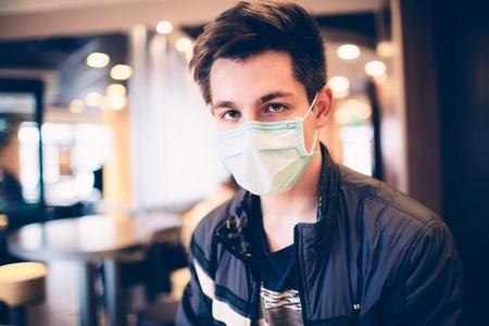 Foto de Man wearing medical face mask in the a restaurant. Male wearing face mask, protection from virus infection. - Imagen libre de derechos
