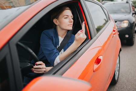 Foto de A woman feels stress on the road. Shows the fact in the window. Big Traffic jams. Business woman is late for work - Imagen libre de derechos