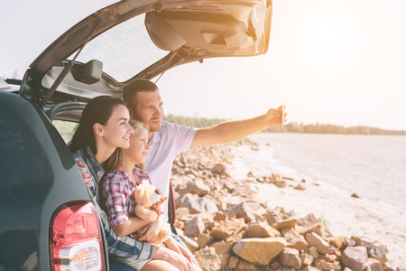 Photo pour Happy family on a road trip in their car. Dad, mom and daughter are traveling by the sea or the ocean or the river. Summer ride by automobile - image libre de droit