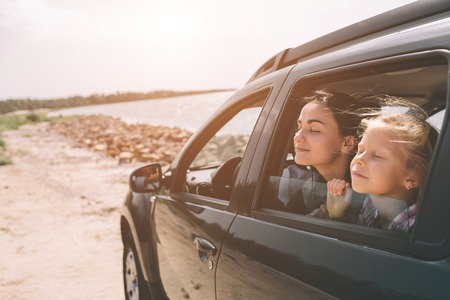 Foto de Happy family on a road trip in their car. Dad, mom and daughter are traveling by the sea or the ocean or the river. Summer ride by automobile. - Imagen libre de derechos