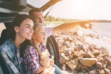 Foto de Happy family on a road trip in their car. Dad, mom and daughter are traveling by the sea or the ocean or the river. Summer ride by automobile - Imagen libre de derechos