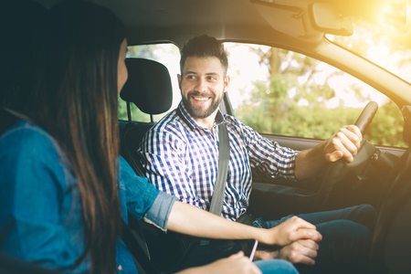 Photo pour Careful driving. Beautiful young couple sitting on the front passenger seats and smiling while handsome man driving a car - image libre de droit