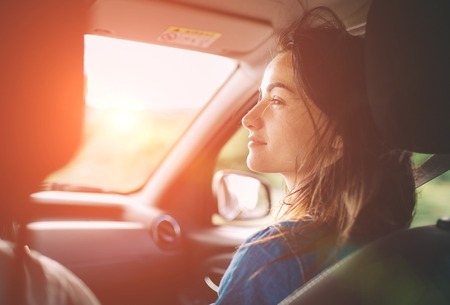 Photo pour Beautiful woman smiling while sitting on the front passenger seats in the car - image libre de droit