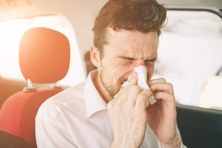 from a young man with handkerchief. Sick guy has runny nose. man makes a cure for the common cold in the car