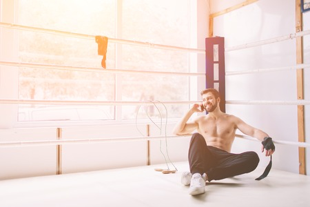 Handsome bearded boxer with bare torso is practicing at the fight club
