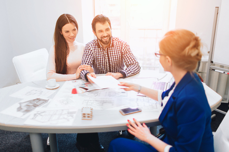 Confident Broker With Home Sellers Behind. Young family couple purchase rent property real estate . Agent giving consultation to man and woman. Signing contract for buying house or flat or apartments