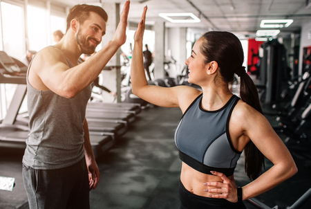 Foto de A beautiful girl and her well-built boyfriend are greeting each other with a high-five. They are happy to see each othr in the gym. Young people are ready to start their workout. - Imagen libre de derechos