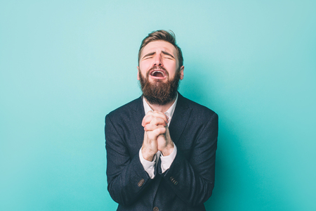 Photo for Guy is standing and holding his hands together. He is praying and begging. Also he is yelling. Isolated on blue background - Royalty Free Image