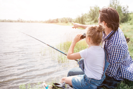 Photo for Man is sitting on grass near water with his daughter and pointing forward. Girl is looking there through binoculars. He is holding fishing rod in hands. - Royalty Free Image