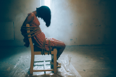 Girl is sitting alone. Her hands and legs are tied with ropes to the chair.