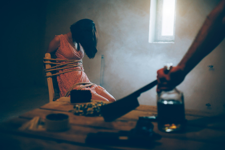 A picture of girl sitting on chair and tied with ropes. She is without consciousness. Brunette girl is sitting near small window. Room is dark. Mans hand is holding big knife. It is lying on table.