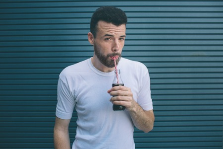 Serious man is drinking coca-cola from bottle through straw. He is looking on camera. Isolated on striped and blue background.