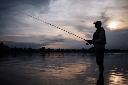 Foto de It is evening outside. Fisherman stands in shallow and fishing. He holds fly rod in hands. There is a reel under it. He stands without moving. - Imagen libre de derechos