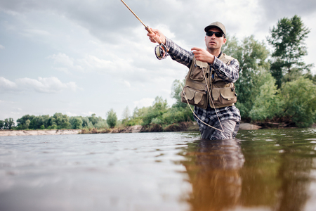 Photo pour Fisherman in action. Guy is throwing spoon of fly rod in water and holding part of it in hand. He looks straight forward. Man wears special protection clothes. - image libre de droit