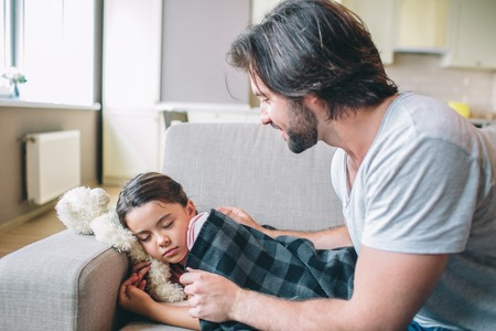 Photo pour Careful parent is covering his daughter with blanket. She fell asleep. Guy looks at er and smiles. - image libre de droit