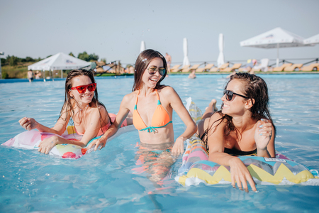 Photo pour Happy models are in swimming pool. They pose on camera. Two models are lying on floats and look at woman in middle. She stands in water and smile. - image libre de droit