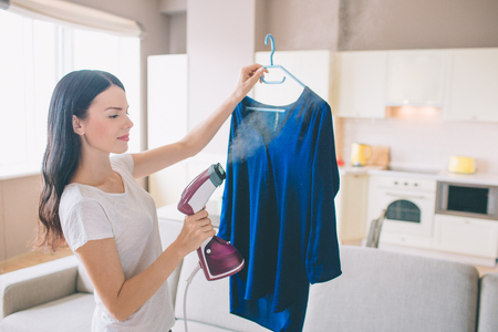 Foto de Woman is steaming blue shirt in room. She holds small stream iron in hand. Brunette is concentrated on work. - Imagen libre de derechos