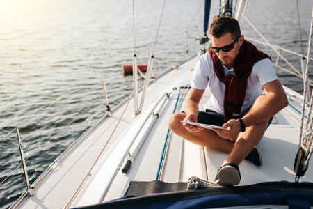 Foto de Serious and peaceful guy sits on board of yacht. He holds and looks at tablet. Young man is calm. He wears white sirt and dark sweater with shorts. - Imagen libre de derechos