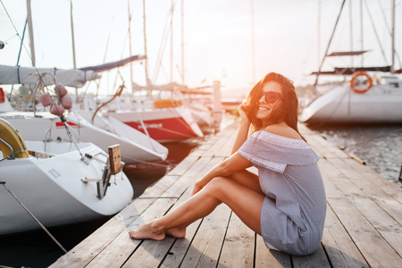 Foto de Gorgeous model sits on pier and smiling. She poses. Young woman keeps legs together and holds hair with hand from waving. She looks happy. - Imagen libre de derechos