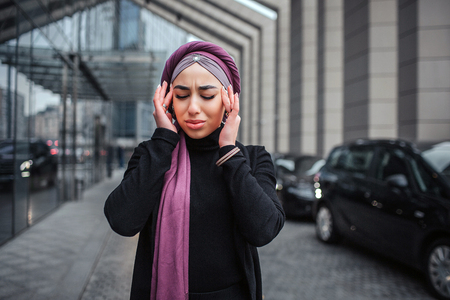 Picture of young arabian woman stand outside. She hold hands close to head and keeps eyes closed. Model has headache. She suffers.