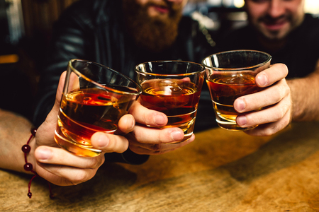 Foto de Cut view of three bearded young men holding glasses with rum together. They smile. People sit in bar - Imagen libre de derechos