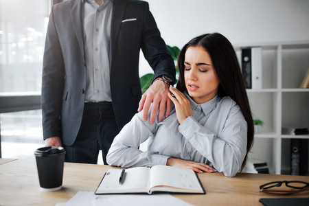 Foto de Concept harassment. Afraid young woman sit at table. Harrasment goes out of her boss. He keep hand on her shoulder. Guy wat to have sex with model - Imagen libre de derechos