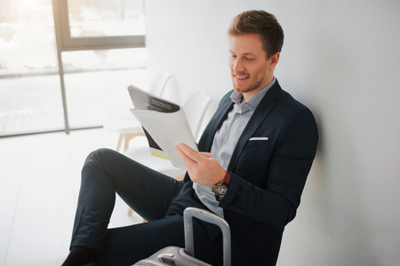 Photo for Cheerful young businessman sit on chair in white room. He read newspaper and smile. Guy wait for flight. - Royalty Free Image