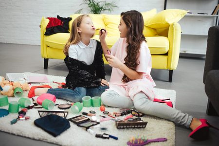 Foto de Brunette girl sitting on carpet in room with her friend and putting lipstick on her lips. Blonde teenager concentrated. - Imagen libre de derechos