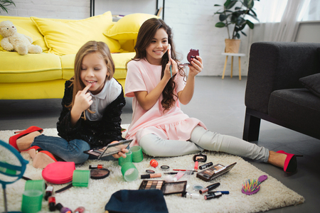 Photo pour Cheerful ans exited girls sitting on floor in room. They doing makeup. Teenagers look in mirror and use cosmetics. - image libre de droit