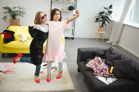 Photo pour Stylish young teenagers stand in room and pose on phone camera. They wear clothes for adult women. Brunette hold camera. They take selfie. - image libre de droit