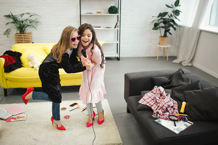 Foto de Teenage girls on high heels holding together microphone and sing into it. They wear clothes and shoes for adult women. Gils have fun and enjoy. - Imagen libre de derechos