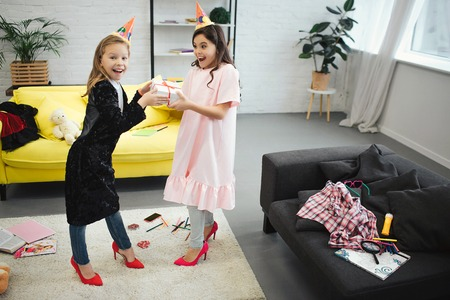 Foto de Two teenagers have fun. They stand in room and hold one gift together. Girls wear clothes and shoes for adult women. They have birthday party. - Imagen libre de derechos
